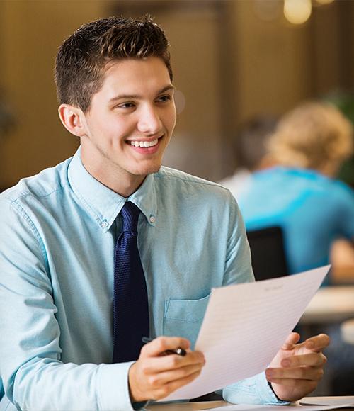 man smiling holding paper